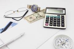 Table blanche de bureau avec les verres et le billet de banque de calculatrice de stylo Photos stock