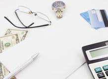 Table blanche de bureau avec les verres et le billet de banque de calculatrice de stylo Photo stock
