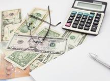 Table blanche de bureau avec les verres et le billet de banque de calculatrice de stylo Image libre de droits