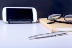 Table blanche moderne de bureau avec l'ordinateur portable, le smartphone et autre approvisionnements Page vide de carnet pour l' image libre de droits