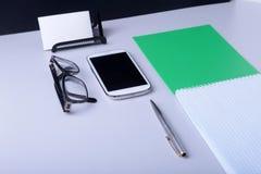 Table blanche moderne de bureau avec l'ordinateur portable, le smartphone et autre approvisionnements Page vide de carnet pour l' photos libres de droits