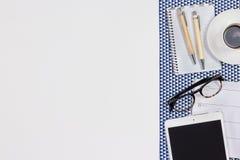 Table blanche moderne de bureau avec un journal intime de carnet, stylos, eyeg Image stock