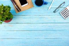 Table bleue de bureau avec l'ordinateur, le stylo et une tasse de café, sort de choses Vue supérieure avec l'espace de copie Images stock