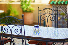 Table with blue ceramic ash tray ain cozy Moroccan cafe Royalty Free Stock Photos