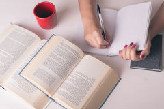 Table with books and coffe and female hands Stock Photos