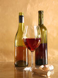 On the table a bottle of wine and a glass of.  stock photography