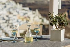 Table with a bottle of wine and glasses. On the background of Santorini, Greece royalty free stock images