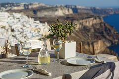 Table with a bottle of wine and glasses. On the background of Santorini, Greece royalty free stock photos