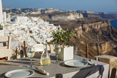 Table with a bottle of wine and glasses. On the background of Santorini, Greece stock photos
