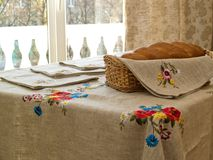 Table with bread and table-cloth. Table with table-cloth in interior in sunny day Stock Photo