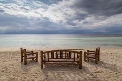 A table with brown chairs. On the shore of a sandy beach overlooking the sea and clouds. Stock Images