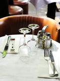 Table at a cafe. Dinner table at cafe set for two with wine glasses, napkins, knives and forks Stock Photography
