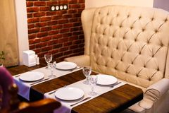 Table in a cafe, serving in a cafe, a vintage beige sofa, wooden table and a brick wall stock photography