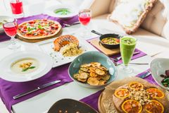Table in cafe with vegetarian dishes - pizza, salads, pie and drinks. Food in restaurant. Table in cafe with vegetarian dishes - pizza, salads, pie and drinks stock images