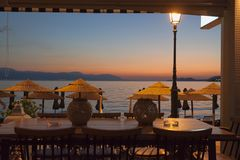 Table in the cafe on the waterfront of Loutraki, Greece. Evening after sunset Royalty Free Stock Photo