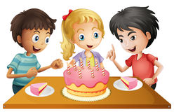 A table with cake surrounded by three kids Royalty Free Stock Image