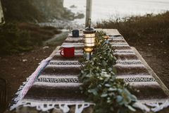 Table at campsite with mugs and lantern Royalty Free Stock Image