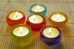 Table Candles. Cheerful candles in colorful glass holders Stock Photos