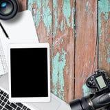 Table carrée de bureau de photographie de bureau avec l'ordinateur portable, le comprimé, l'appareil-photo et le verre sur le bac Photo stock