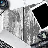Table carrée de bureau de photographie de bureau avec l'ordinateur portable, le comprimé, l'appareil-photo et le verre sur le bac Photo libre de droits