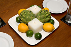 Table centerpiece. Contemporary centerpiece with candles, artichokes, lemons and limes royalty free stock images