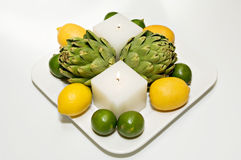Table centerpiece. Contemporary centerpiece with candles, artichokes, lemons and limes stock photos