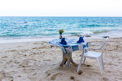 Table and chair and a blue table-cloth on the beach. Chair an table with blue table-cloth on a Thai beach, against the blue ocean Royalty Free Stock Photos