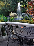 Table, Chair and fountain. Table with drink and fountain in the background Royalty Free Stock Image