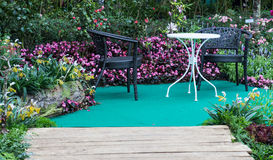Table and chair in hedge of garden. Wood sidewalk lead to table and chair in hedge of garden Stock Photo