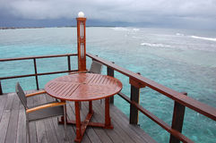Table and chair at open air cafe with ocean view Stock Photos