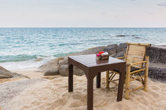Table and chair on a rocky Thailand beach. A table and chair among the rocks, next to the sea Royalty Free Stock Images