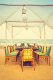 Table and chair set on the beach for dinner Stock Photos