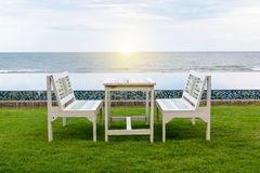 Table and chair, swimming pool and the beach Royalty Free Stock Images