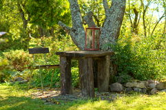 Table chair under tree in garden Stock Images