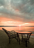 Table and chair by the water at sunrise Royalty Free Stock Photo