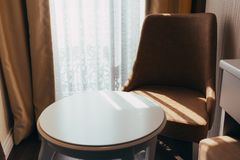 Table with a chair by the window on a sunny day stock images