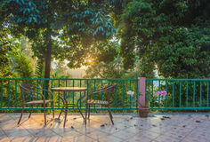 Table and chair on wood deck in the garden with sunset Stock Photo
