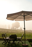 Table and chairs. Table, chairs and umbrella near a meadow Stock Photos