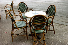Table and chairs. Small round table green and white patterned chairs sitting outside by the street Stock Photography