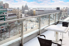 Table and chairs on balcony. In snow at winter day. View of city. Focus on table, closest chair Stock Images