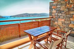 Table and chairs on a balcony with sea view, Greece Stock Image