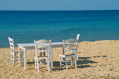 Table and chairs on the beach. Romantic family dinner at the sandy beach Royalty Free Stock Photography
