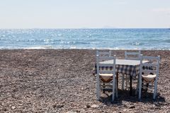 Table with chairs on the beach. Tavern in Greece, Santorini Stock Photo
