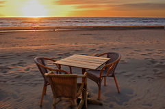 Table and chairs in cafe on the beach at sunset Royalty Free Stock Images