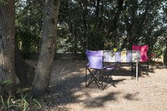 Table and chairs on campsite. Between the trees royalty free stock image