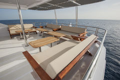 Table and chairs on deck of a luxury motor yacht stock photography