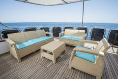 Table and chairs on deck of a luxury motor yacht. Rear teak deck of a large luxury motor yacht with chairs sofa table and tropical sea view background Royalty Free Stock Photography