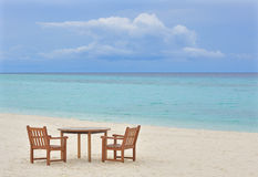 Table and chairs on empty beach Stock Photos