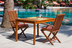 Table and chairs in empty cafe next to the swimming pool, Thailand Stock Photos