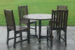 Table and Chairs on an empty patio on a rainy day. Viewed through a rain drenched window this set of wooden patio table and chairs sits empty stock images